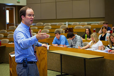 Professor Dustin Buehler introduces first-year law students to the basics of civil procedure in the law school's 200-seat E.J. Ball Courtroom.  Photo Russell Cothren